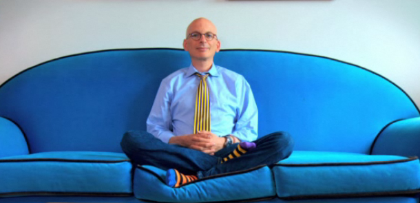 Seth--Godin--sitting--on--a--blue--couch