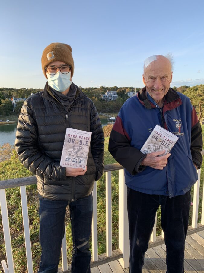 Chuck Daly with his son and co-author Charlie Daly hold copies of his memoir Make Peace or Die